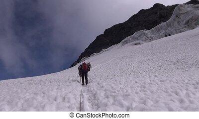 Climbing on a snow slope - Mountaineer climbs a steep iced...