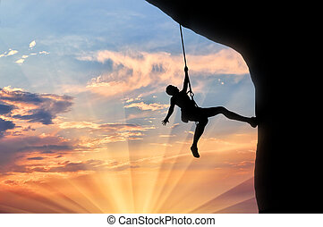 Mountaineer climbs cliff sunset - Climber on the rope climbs...