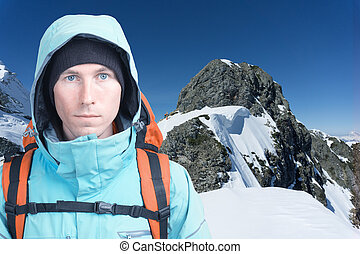 Mountaineer man looking at the camera, in the background high mountains. Close-up portrait.