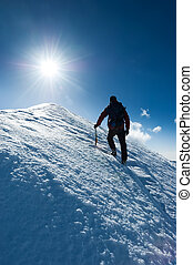 Mountaineer reaches the summit of a snowy peak. Concept: courage