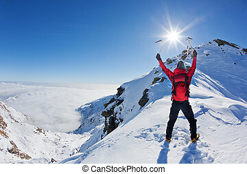 Mountaineer reaches the top of a snowy mountain in a sunny ...