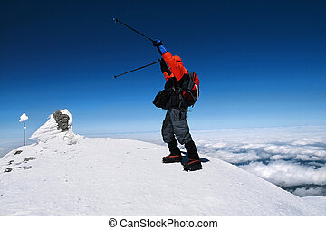 Mountaineer reaches the top of a snowy mountain in a sunny winter day. Travel sport lifestyle concept