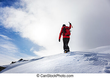 Mountaineer reaching the summit of a snowy peak in winter season.