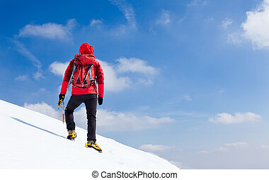 Mountaineer walking uphill along a snowy slope.