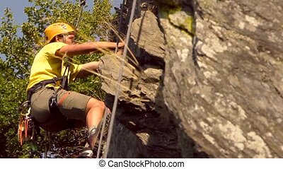 Mountaineering - Young man, climbing up an almost vertical...