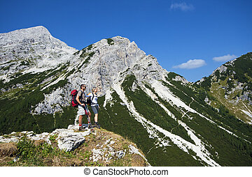 mountaineering - Young man and woman on a sunny day hiking...