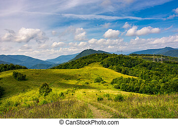 mountainous countryside in early autumn. path through grassy...
