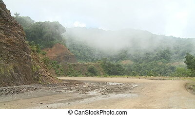 Mountainous Forest, Road and Mist - Steady, wide shot of...