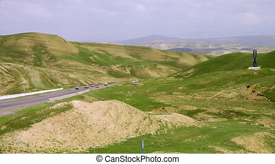 Mountainous Green Hills and Vehicles on Road - Steady, wide...