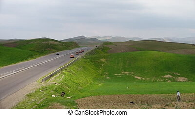 Mountainous Hills, Vehicles on Road and Man Plowing Field -...