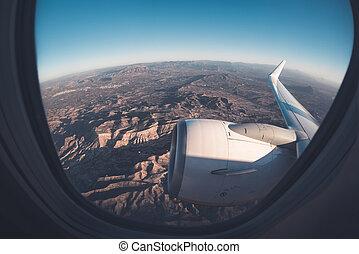 Mountainous window seat view from airplane