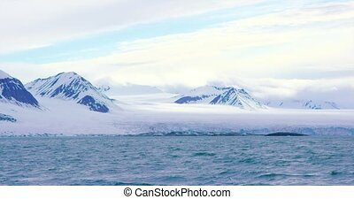 Mountains and a massive glacier in the arctic - The large...