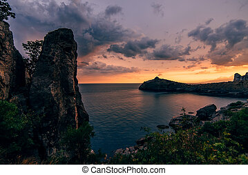 mountains and sea on background of beautiful sunset sky with clouds