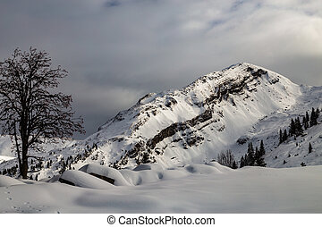 Mountains covered with snow and surrounded by clouds