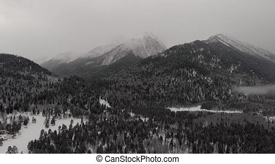 Mountains forest snow Russia grayness overcast shooting flight from above clouds fog Russia Arkhyz .