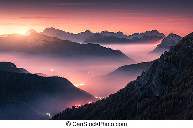 Mountains in fog at beautiful sunset in autumn in Dolomites, Ita