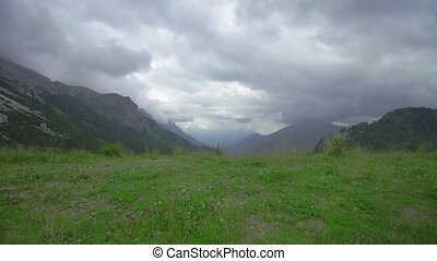 Mountains in the Alps, covered by greenery with clouds flowing overhead