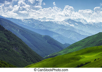 Mountains nature landscape on sunny summer day. Mountains ranges in Svaneti, Georgia. Scenery Hills and mountain. Amazing mountain range. Alpine. Green meadow covered by grass in highlands