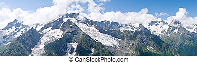 A panoramic view on rocky mountains under clouds