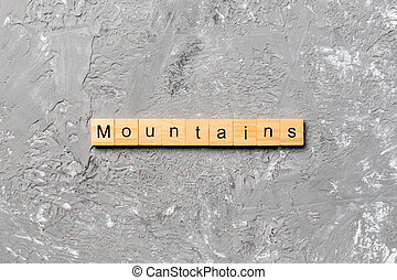 mountains word written on wood block. mountains text on cement table for your desing, concept