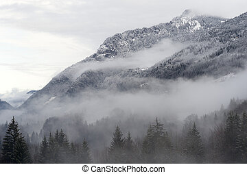 Mountainvalley. - Mountain valley with snow and low clouds.