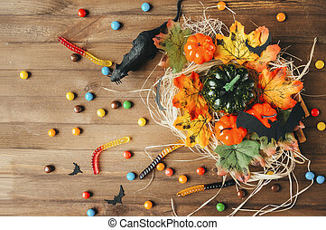 mouse, candy, bats, pumpkin on hay on rustic background, autumn, Halloween,
