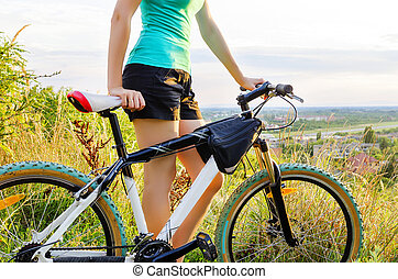 Moutain bike woman at the sunset standing on a hill