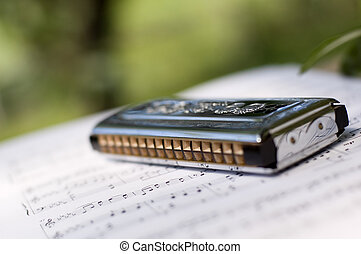 mouth harmonica on sheet music close up