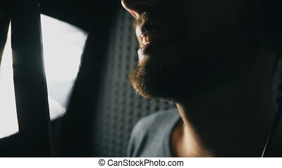 Mouth of male singer singing in sound studio. Unrecognizable man recording new song. Guy with beard sings to microphone. Working of creative musician. Show business concept. Slow motion Close up