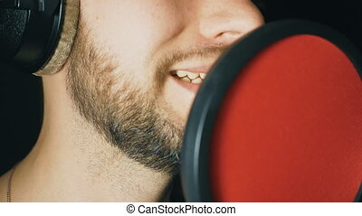 Mouth of male singer singing in sound studio. Unrecognizable man recording new song. Guy with beard sings to microphone. Working of creative musician. Dark background. Slow motion Close up
