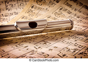 Mouthpiece of flute old handwritten sheet music elevated view