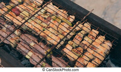 Mouthwatering different kinds of meat with grilled vegetables on a barbecue outdoors