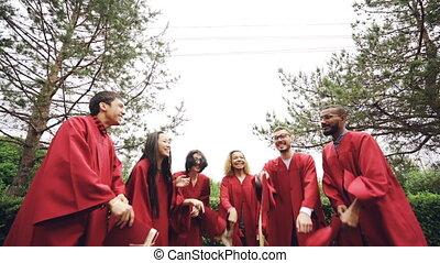 mouvement, lent, coup, ciel, lancement, chapeaux, avoir, jour remise diplômes, education, amusement, rire, bas, traditionnel, campus., angle, jeunesse, concept., grads, heureux