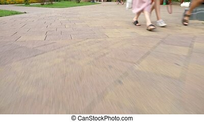 movement along a paved pedestrian walkway. unrecognizable people walk on the road with their feet. A group of tourists, pedestrians crossing the street together. Male and female legs