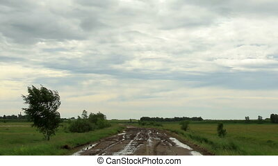 Movement of clouds over a dirt road