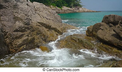 Movement of sea water between the rocks on tropical beach. Thailand