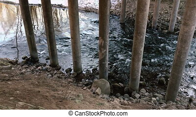 Movement of the river under the bridge in the early spring during the daytime. Side view video.