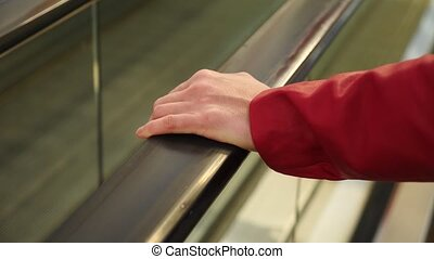 movement of the woman's hand on the escalator handrails. 4k,...