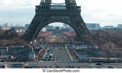 Movement under Tour Eiffel in a current of day: cars, tourists. Paris, France. Time lapse.