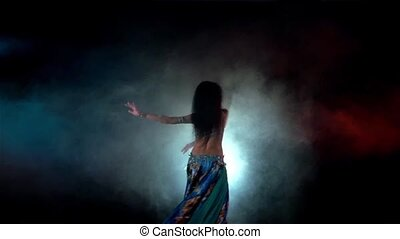 Movements of beautiful woman finishing belly dance in blue dress with long dark hair , back light, red, blue, in smoke, slow motion