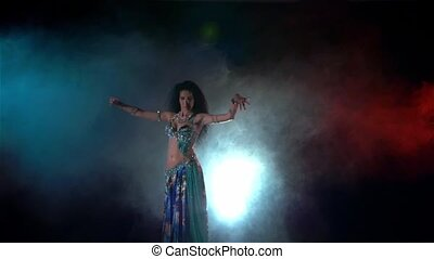 Movements of young woman finishing belly dance in blue dress with long dark hair , back light, red, blue, smoke, slow motion