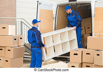 Movers Unloading Furniture From Truck - Young male movers...