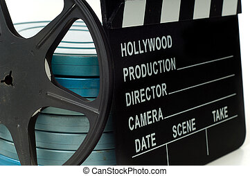 Hollywood Movie clabboard with movie tins and an empty reel on white background