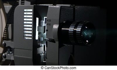 Movie projector that turns the film reel. Side view - Movie...