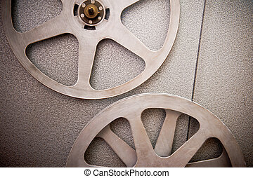 Movie reels part with filmstrip crossing on projector detail, 16 mm film format in vintage colors