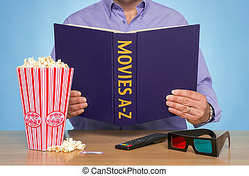 Movies A-Z - A man sat at a table reading a MOVIES A-Z book