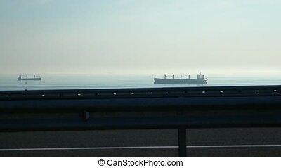 Moving a cargo ship far away in the sea.