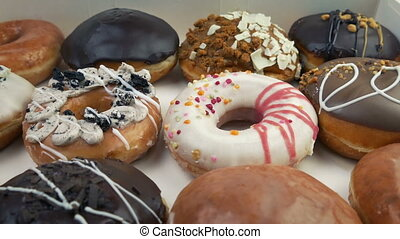 Moving Across Box Of Mixed Donuts - Moving slowly over many...