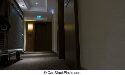 Moving along hotel feeble lighted hallway - While the hotel...