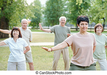 Moving arms at qigong practice - Active mature people ...